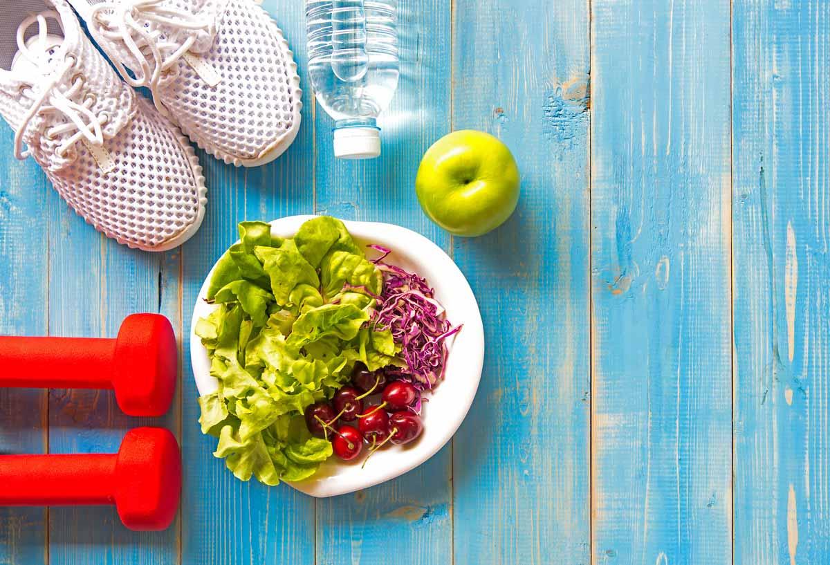 Vitaminer, Mineraler, Trening: Bilde av sko, vekter, salat, eple og vannflaske på blå bakgrunn