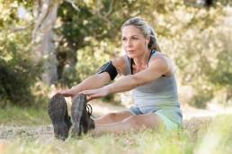 Restitusjon: Kvinne som sitter på bakken i grønne omgivelser og tøyer ut.