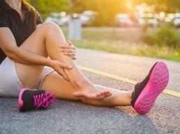 kvinnelig løper holder seg til leggen